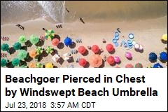 Windswept Beach Umbrella Pierces Woman's Chest