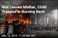 Riot Leaves Mother, Child Trapped in Burning Bank